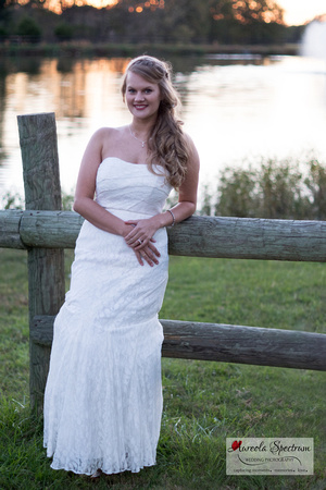Bride leans on fence in front of lake in Monroe, NC