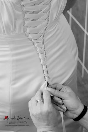 Bridesmaid ties back of wedding dress