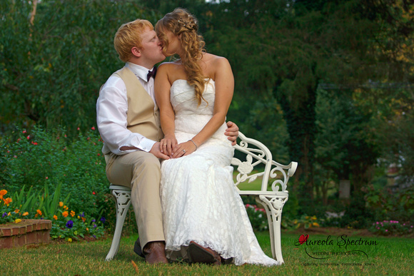 Bride & groom sit on white bench and kiss