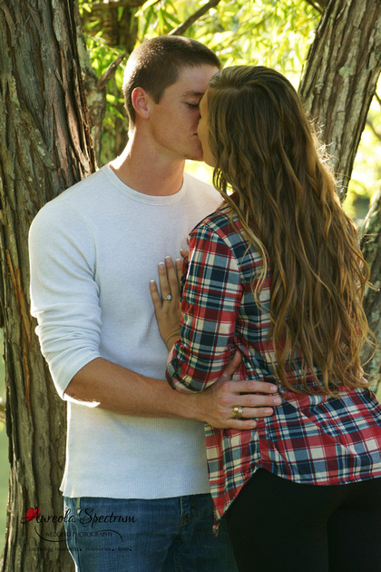 Couple kisses by tree in Lake Lure, NC