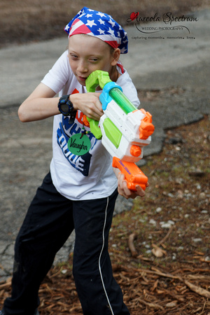 Heart kid plays with water gun at camp luck.