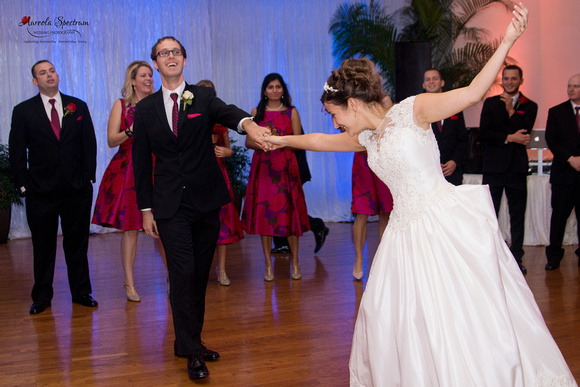 Groom twirls bride during first dance.