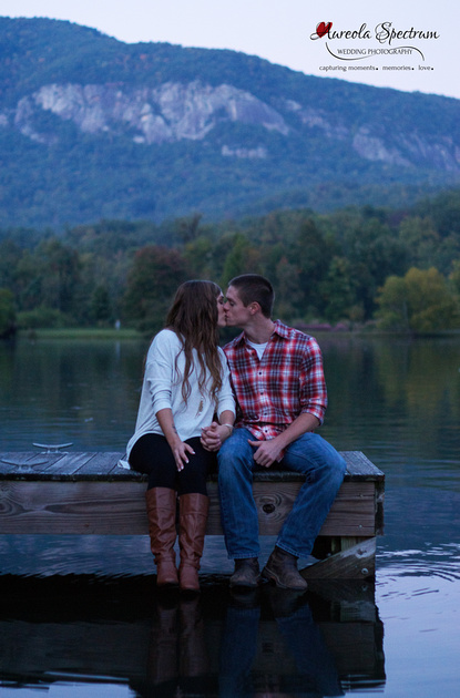 Couple sits on dock and kisses in Lake Lure, NC