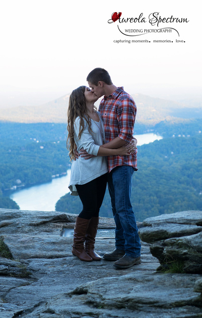 Engaged couple kiss at Chimney Rock overlook