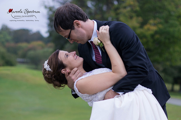 Bride and groom's portrait as they dip on a golf course.