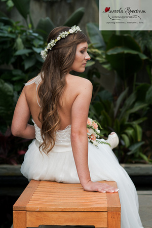 Bride sits on a bench in the orchid conservatory in NC.
