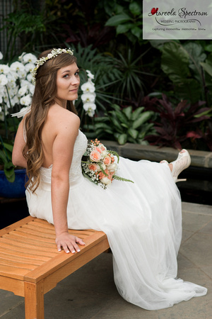 Bride sits on a bench at NC botanical garden.