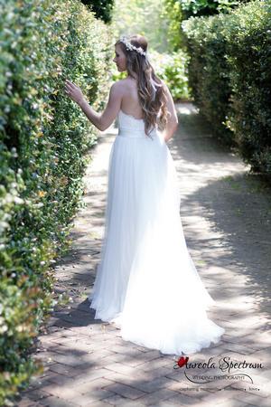 Bride walks along the hedges at Daniel Stowe Botanical Garden.
