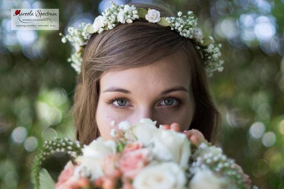Bride hides face behind her flower bouquet.