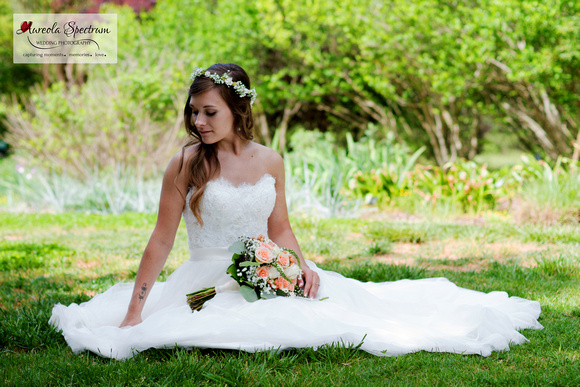 Bride sits in a meadow at Daniel Stowe Botanical Garden.