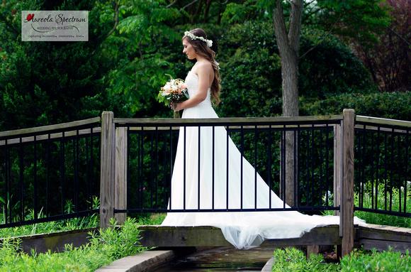 Gorgeous bride stands on bridge at botanical garden.