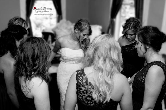 Bride praying with Bridesmaids