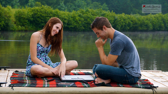 Couple plays scrabble on the dock of a lake