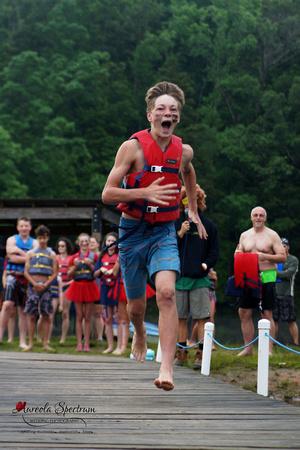 Heart kid runs down docks at camp luck family camp.