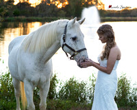 Bride standing with horse in front of pond