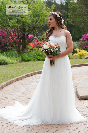 Bride stands near colorful flowers.