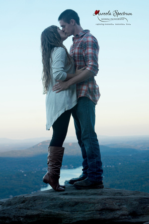 Engaged couple kisses on the overlook at Chimney Rock